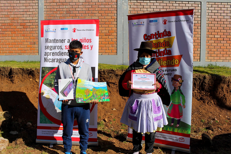 """Ramón* junto a su madre Rita* recibiendo el premio del concurso de expresión artísticas """"Pequeños artistas, grandes héroes""""."""